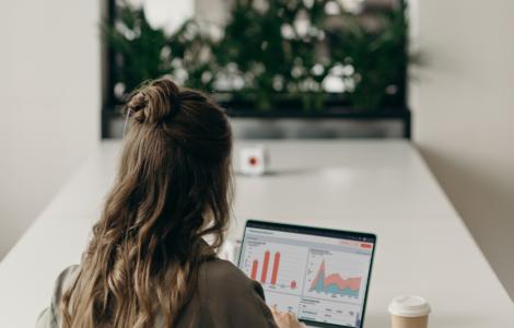 Marketing professional reviewing HubSpot Marketing Hub Dashboard on laptop